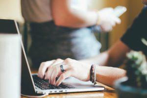 komputer, laptop, dłonie, bransoletki, długopisy,biurko